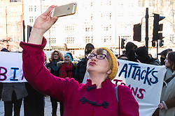 Anti-transgender feminist Venice Allan, 42, takes a selfie against a backdrop of transgender rights activists demonstrate outside Westminster Magistrates' Court to &quot;Free the Shewolf&quot;, Tanis Jacob Wolf / aka Tara Flik Wood who is facing a charge of assault by beating of a 60 year old woman at Speaker&rsquo;s Corner in Hyde Park, London in September 2017.<br /> <br /> Wolf/Wood, 26, entered a plea of not guilty and was bailed to appear at Hendon Magistrates&rsquo; Court in two months&rsquo; time. London, February 15 2018.