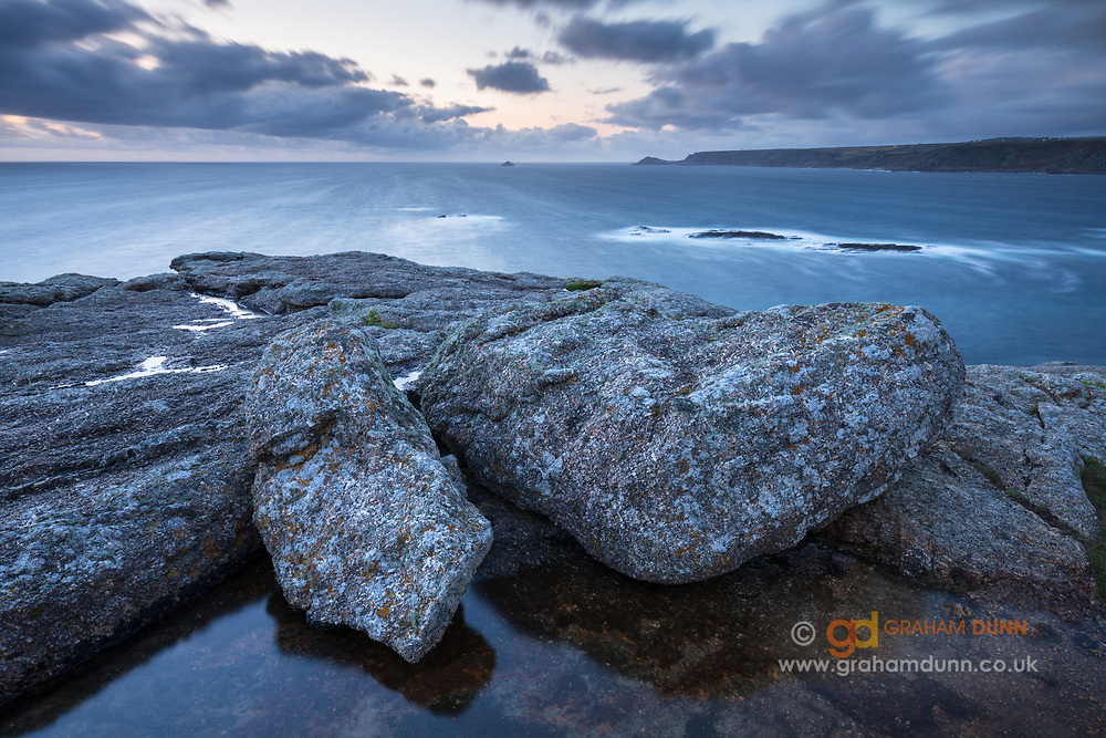 Long exposure at dusk, looking out from Sennen Cove rocks towards Cape Cornwall. Dramatic English coastline in summer, July.