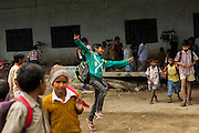 27th March 2014, Shakarpur, New Delhi, India.  A child jumps for joy as classes end and he leaves a makeshift school under a metro bridge near the Yamuna Bank Metro station in Shakarpur, New Delhi, India on the 27th March 2014<br /> <br /> Rajesh Kumar Sharma (born 01/02/1970), started this makeshift school in 2011. Six mornings a week he teaches underprivileged children for three hours while his younger brother replaces him at his general store in Shakarpur. His students are children of labourers, rickshaw-pullers and farm workers. This is the 3rd site he has used to teach under privileged children in the city, he began in 1997. <br /> <br /> PHOTOGRAPH BY AND COPYRIGHT OF SIMON DE TREY-WHITE<br /> + 91 98103 99809<br /> email: simon@simondetreywhite.com<br /> photographer in delhi<br /> journalist