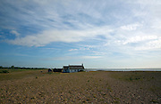 Isolated bungalow at the mouth of the River Ore near the end of Orford Ness spit, Shingle Street, Suffolk, England