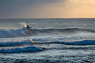 Surfers on the Pacific Ocean  off the island of Kauai, Hawaii