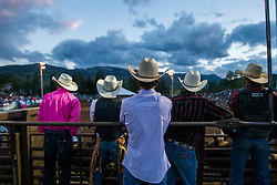 Cowboys look on from the chute during the bull riding competition.