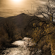 A silhouette of Lookout Mountain (background) and Clear Creek (foreground) in Golden, Colorado, just outside Denver at the eastern edge of the Rocky Mountains.