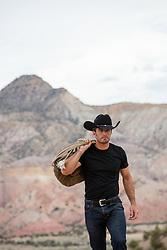 cowboy with a duffle bag walking on a mountain range