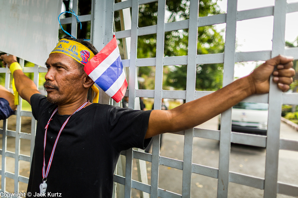 24 DECEMBER 2013 - BANGKOK, THAILAND: An anti-government protestor blocks the gate into the Thai-Japan Stadium during a protest in Bangkok. Hundreds of anti-government protestors are camped out around the Thai-Japan Stadium in Bangkok, where political parties are supposed to register for the election on February 2. As of Dec 24, nine of the more than 30 parties were able to register. Protestors hope to prevent the election. The action is a part of the ongoing protests in Bangkok that have caused the dissolution of the elected government.      PHOTO BY JACK KURTZ