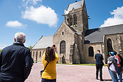 May 30, 2019, Sainte-Mère-Église, Normandy, France.<br /> Tourists photographe the  parachute with an effigy of Private Steele in his Airborne uniform that hangs from the steeple of the village church. <br /> 30 Mai 2019, Sainte-Mère-Église, Normandie, France. Des touristes photographient un parachute avec une effigie du soldat Steele suspendu au clocher de l'église du village.