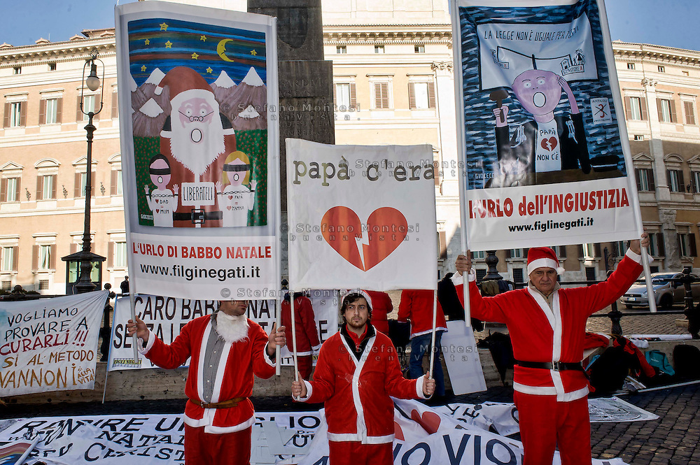 "Roma 21 Dicembre 2013<br /> L'associazione «Figli Negati» e il movimento pacifista «Armata dei padri», vestiti da Babbo Natale, manifestano  a piazza Monte Citorio,  a Roma,  per fare gli auguri di buon natale ai figli «rapiti» da uno dei due genitori dopo la separazione.<br /> Rome December 21, 2013<br /> The association ""Children Denied"" and the  movement ""Army of the Fathers"", dressed as Santa Claus, manifest in Monte Citorio square in Rome to wish Merry Christmas to their children ""kidnapped"" by one of the parents after the separation."
