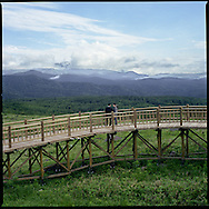 A couple takes in the view over a meadow frequented by brown bears from a raise boardwalk fitted with electrified wire to separate brown bears from human visitors, near the Shiretoko Five Lakes, Shiretoko National Park, an UNESCO World Heritage Site, Hokkaido, Japan.
