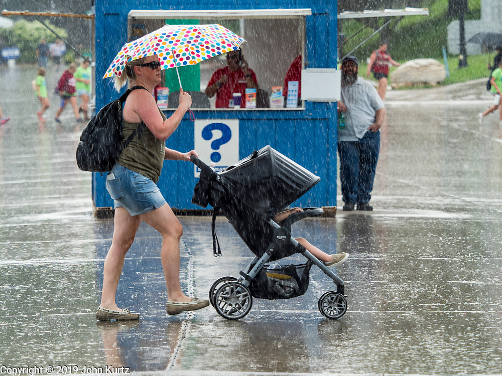 08 AUGUST 2019 - DES MOINES, IOWA: People walk through the rain on the first day of the Iowa State Fair. The Iowa State Fair is one of the largest state fairs in the U.S. More than one million people usually visit the fair during its ten day run. The 2019 fair run from August 8 to 18.           PHOTO BY JACK KURTZ