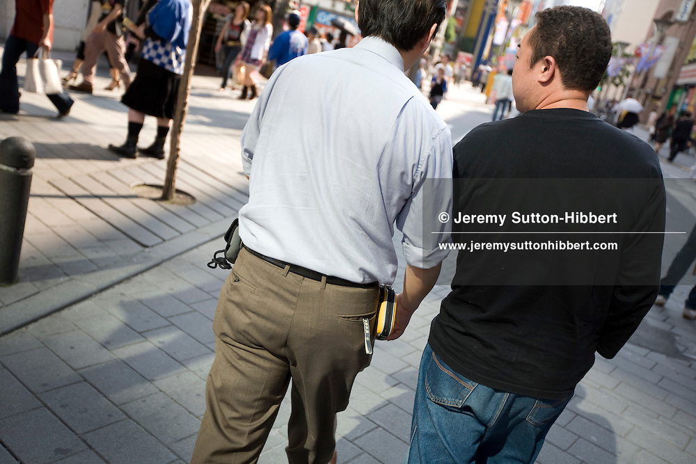 Osamu Toumiya (in blue shirt, centre of pic), CEO of Global Network Corporation - a Private Investigation company, walks with a fellow operative towards a 'mission rendezvous',  in the Ikebukuro district of Tokyo, Japan. Monday, June 16th, 2008...
