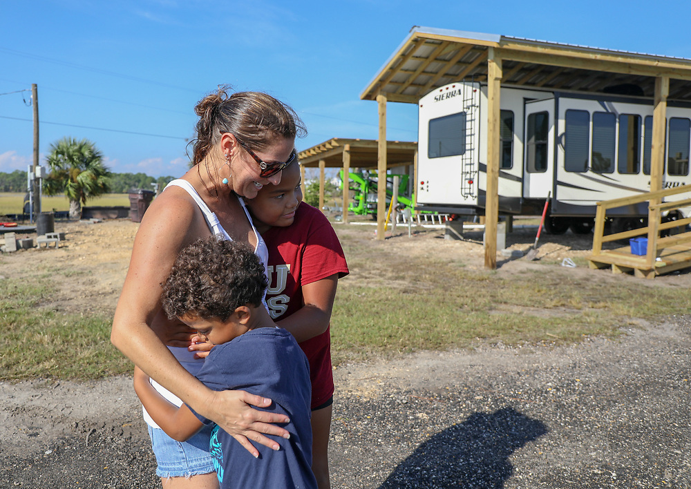 CHRIS URSO   |   Times<br /> Dianthe Aibejeris, 40, of Fort Lauderdale hugs her best friend's children Alyssa Washington, 11, right, and her brother Jamison Thursday, Oct. 11, 2018 in Keaton Beach. Aibejeris and her family operate a small trailer campground on the coast of the Gulf of Mexico. Although they had four feet of water from Hurricane Michael cover the campground Aibejeris and her family didn't sustain any damage unlike when Hurricane Hermine barreled through the area in 2016.