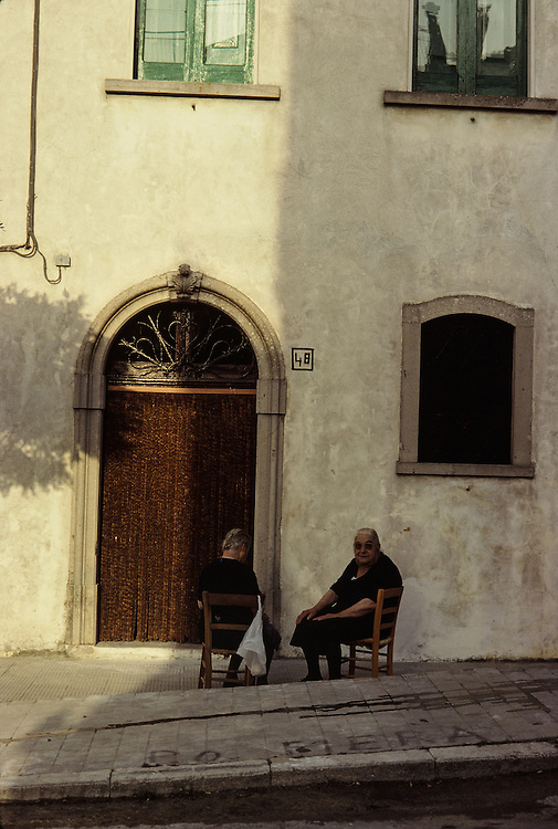 two elderly women sitting in chairs by their home outside