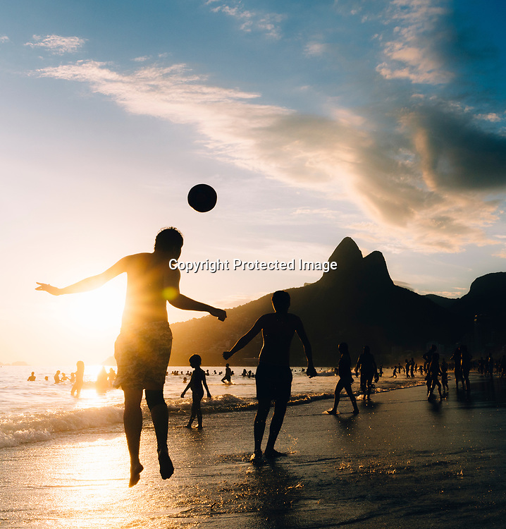 Two young men play Keepy-Uppy in Portuguese altinho on the beach in Ipanema, Rio de Janeiro, Brazil at sunset