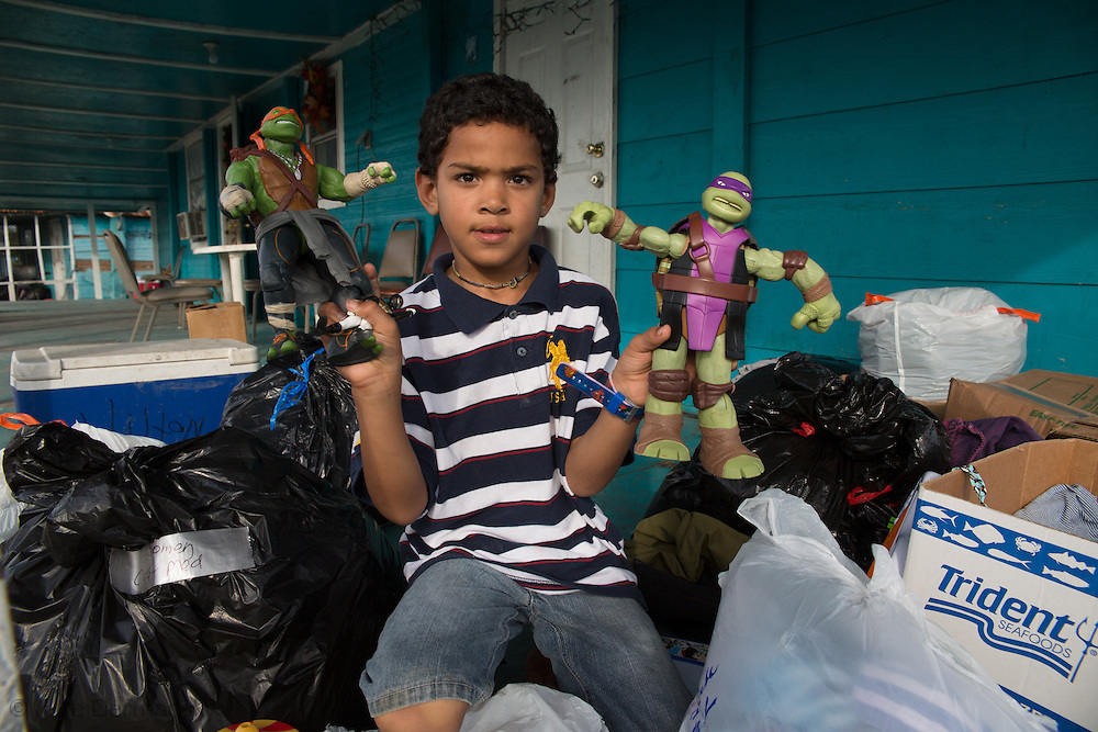 Boy play with donated Christmas gifts on Isle de Jean Charles.