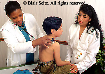 African American Female Doctor, Physician at Work, Urban Clinic, Hispanic Mother Attends Child, Hispanic Boy Patient