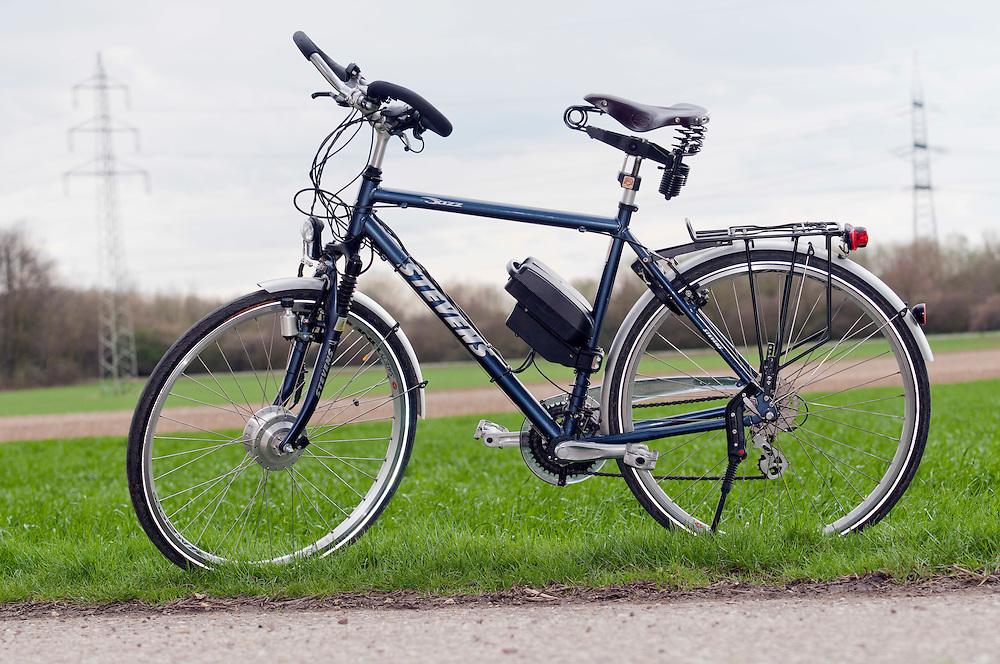 Elektrofahrrad an einem Feldweg geparkt vor Acker und Stromleitung   |  an e-bike standing in the landscape  in front of electronic  wires   | .