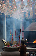 A woman lighting incense sticks in the Thien Hau Pagoda in Ho Chi MInh City, Vietnam, Southeast Asia