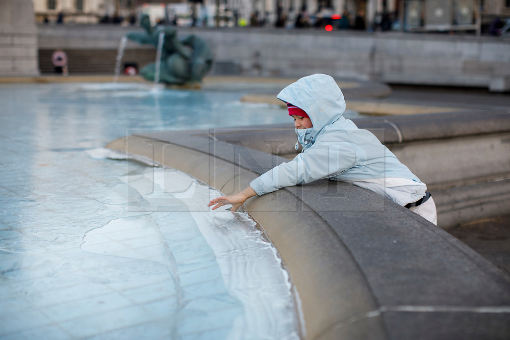 © Licensed to London News Pictures. 12/12/2017. London, UK. Devon Meharry reacts to frozen water fountains in Trafalgar Square, London as temperatures drop bellow -3C across the capital overnight on Tuesday, 12 December 2017. Photo credit: Tolga Akmen/LNP