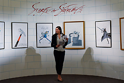 "© Licensed to London News Pictures. 31/03/2017. London, UK. A staff member stands in a wall containing works by Gerald Scarfe. The wall references Scarfe's contribution to Pink Floyd's ""Another Brick in the Wall"".  Press preview of ""Made in Britain"" at Sotheby's in New Bond Street.  The auction on 5 April celebrates innovative British art in the twentieth century as well as artwork by political cartoonist Gerald Scarfe. Photo credit : Stephen Chung/LNP"