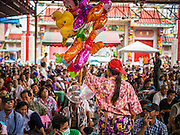 """09 AUGUST 2014 - BANGKOK, THAILAND:       An inflatable toy vendor sells to people waiting for free meals at the Ruby Goddess Shrine in the Dusit section of Bangkok. The seventh month of the Chinese Lunar calendar is called """"Ghost Month"""" during which ghosts and spirits, including those of the deceased ancestors, come out from the lower realm. It is common for Chinese people to make merit during the month by burning """"hell money"""" and presenting food to the ghosts. At Chinese temples in Thailand, it is also customary to give food to the poorer people in the community.   PHOTO BY JACK KURTZ"""