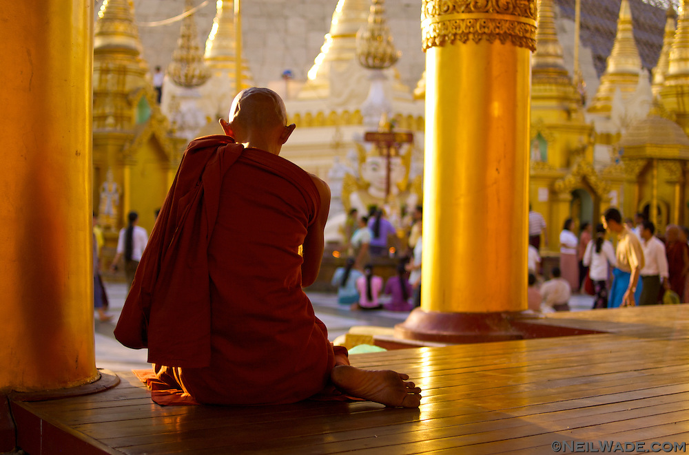 An elderly Buddhist monk meditates at busy Shwedagon Pagoda in Yangon (Rangoon), Myanmar (Burma).