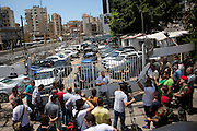 Reporters, soldiers and members of the public stand outside a car dealership that was hit by a rocket, in the Hezbollah neighbourhood of Dahieh, in south Beirut, Lebanon. The day after a speech by Hezbollah leader Hassan Nasrallah, in which he confirmed the group was actively fighting in Syria, two rockets hit the south Beirut Hezbollah stronghold of Dahieh. One rocket hit a car dealership with the other striking an apartment, no-one was killed in the attack and no group admitted responsibility.