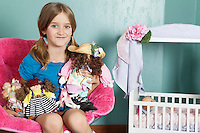 Portrait of a little girl with stuffed toys sitting on chair by doll's crib