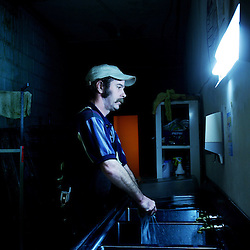 Kyle Green | The Roanoke Times<br /> November 15, 2006 Sparky's Food Mart employee, Thomas Secrest washes dishes inside of the store located at 502 Elm Avenue SW in Roanoke, Virginia. Thomas has worked at the store for 2 months.