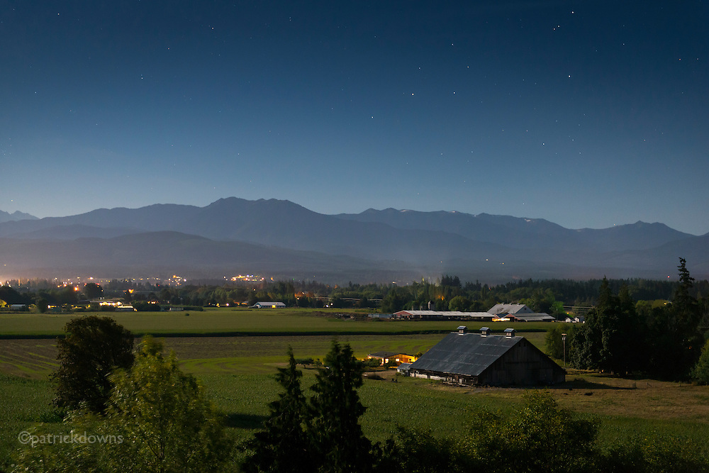 A peaceful Sequim Valley under an almost-full moon. The 100+ year old Lotzegesell barn is at lower right, with the Olympic Mountains standing silent under the stars.