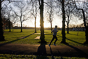 A male jogger exercises in a wide landscape of late winter light of south London's Ruskin Park.