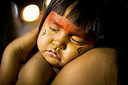 Yawalapiti girl sleeps on mother's shoulder during the event.