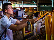 20 OCTOBER 2017 - BANGKOK, THAILAND: People light prayer candles at Chao Zhou Shi Kong Shrine in Bangkok's Chinatown on the first day of the Vegetarian Festival, what Thais call the Taoist Nine Emperor Gods Festival, in the Chinatown neighborhood of Bangkok, Thailand. It is a nine-day Taoist celebration beginning on the eve of 9th lunar month of the Chinese calendar. For nine days people participating in the festival wear only white and don't eat meat, poultry, seafood, and dairy products. The vegetarian festival is celebrated throughout Thailand, but especially in Phuket and Bangkok, cities with large ethnic Chinese communities.       PHOTO BY JACK KURTZ