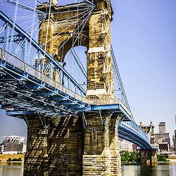 Photo of John A. Roebling Bridge in Cincinnati Ohio. The John A. Roebling Suspension Bridge was built in 1865 and crosses the Ohio River connecting Covington Kentucky with Cincinnati Ohio. The photo is vertical, high resoution and was taken in July 2012.