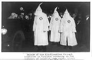 Three members of the Ku Klux Klan in masks and gowns taking part in a night parade. To their left is a car carrying further masked members of the Klan, March 1922 .