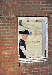 good looking cowboy in a rustic window