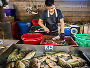 12 JULY 2018 - SAMUT PRAKAN, SAMUT PRAKAN, THAILAND: A worker butchers fish in Pak Nam market in Samut Prakan. Fish consumption recently hit a record high according to a report published this week by the United Nations Food and Agriculture Organization. The FAO reported that global fish production peaked at about 171 million tonnes in 2016, 47 percent of it from fish farming. The FAO also reported that global fish consumption between 1961 and 2016 was rose nearly twice as fast as population growth. In 2015, fish accounted for about 17 percent of the animal protein consumed globally. This has ramifications for Thailand, which has one of the world's largest fish and seafood industries. About 90% of Thailand's seafood production is exported, which accounts for about 4% of Thailand's exports.   PHOTO BY JACK KURTZ