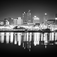 Peoria Illinois at night black and white photo of downtown city skyline buildings reflection on the Illinois River and the Spirit of Peoria paddlewheel riverboat.