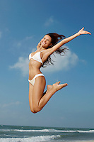 Woman jumping on beach mid-air