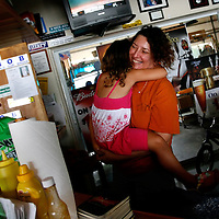 ANNA MARIA ISLAND, FL -- July 9, 2009 -- Manager Peggy Davenport hugs her daughter, Maddi, 5, as she chats with customers, including Liz Christie-Cline, left, at Duffy's Tavern on Anna Maria Island in Manatee County, Fla., on Thursday, July 9, 2009.  (Chip Litherland for The New York Times)