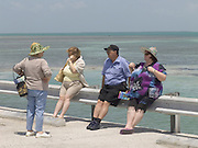 group of tourist sitting and talking along Route One to Key West USA