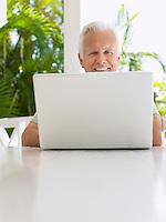 Man using laptop at verandah table