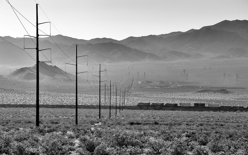 Crossing the desert near the Nevada/California border, this hot westbound  encounters one of the many power lines that cross the landscape.