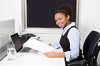 Portrait of smiling businesswoman with document using laptop at desk in office