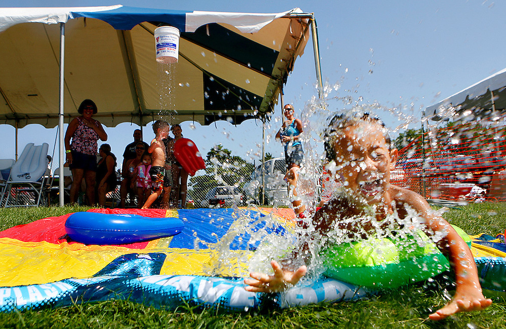 Ethan Wetterling, 4, of Kennewick slips and slides at Story Group's private tent in Pasco in 2009. After the slide ripped, Ryan McMenamin drilled holes in a bucket and routed the hose through it to keep the water flowing for the kids. Pasco was the site of the 1987 riot, but has since become the more family-friendly side.