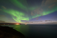 The northern lights shine through evening twilight over the Atlantic Ocean near Ólafsvík, Iceland.