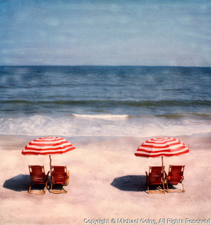 Two red striped beach umbrellas with twin red beach chairs on beach at Hilton Head, SC
