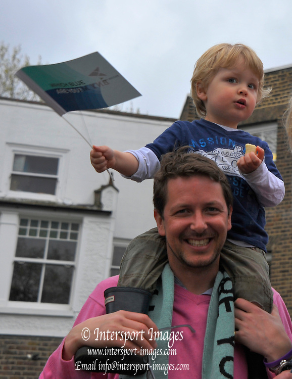 London, United Kingdom.    2014 Varsity Boat Race between Oxford University and Cambridge University Boat Clubs, Championship Course, Putney to Mortlake,  River Thames;   Young supporter, waves his flag. 11:32:59 - Sunday  - 06/04/2014  [Mandatory Credit; Intersport Images].