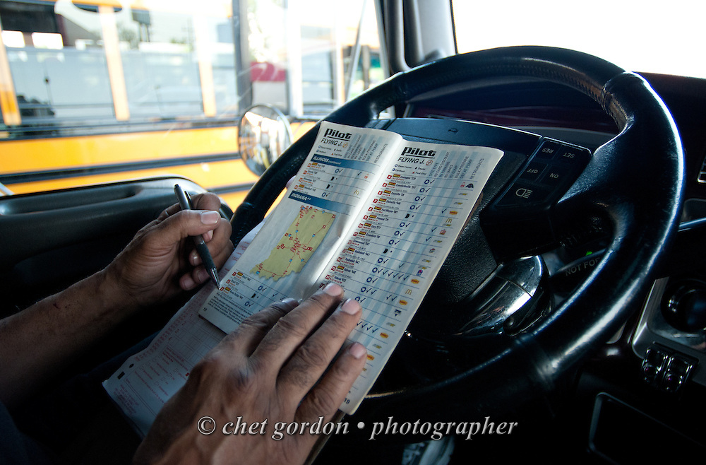 Truck driver Jose Williams checks his truck stop map and other documents during a fuel stop in Saint Peters, MO on Friday, April 17, 2015. Williams, a cross country trucker with a national household moving company, made several delivery stops in central California's Bay Area during the following week with loads that originated in Virginia on April 16th.  © Chet Gordon/THE IMAGE WORKS