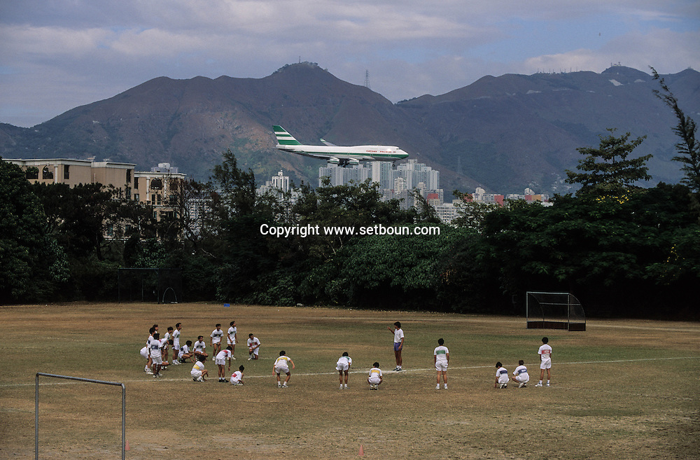Hong Kong. King George Five traditional British school.  / planes landing on Kai tak airport in the the city CENTER over the buildings .      plane landing near the sport ground  / école  - King Georges V -  meeting du matin . / Des avions au ras des buildings. L'ANCIEN AEROPORT DE KAI TAK. avion atterrissant en plein milieu de la ville sur aéroport  Kai Tak / Dans la ville de Hong-Kong surpeuplée, l'avion est le principal moyen d'accès à la ville. La seule piste d'atterrissage est en pleine ville     et avion atterissant  / R82/7    L1069  /  R00082  /  P0001993 King George Five traditional British school. plane landing near the sport ground   / planes landing on Kai tak airport in the the city CENTER over the buildings .        / ecole  - King Georges V -  meeting du matin . / Des avions au ras des buildings. L'ANCIEN AEROPORT DE KAI TAK. avion atterrissant en plein milieu de la ville sur aéroport  Kai Tak / Dans la ville de Hong-Kong surpeuplée, l'avion est le principal moyen d'accès à la ville. La seule piste d'atterrissage est en pleine ville     et avion atterissant  / R82/7    L1069  /  R00082  /  P0001993