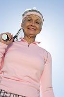 Senior woman holding tennis racket, portrait